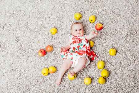 baby girl lying on the floor with Green apples