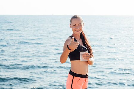 girl drinking water from a shaker after a workout on the beach Stock Photo