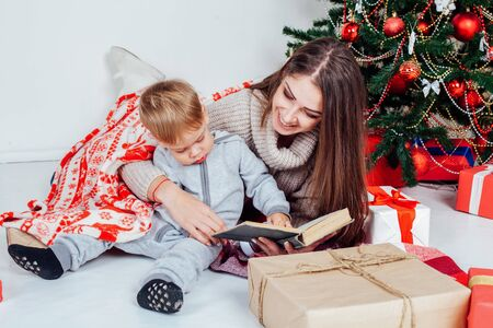 mother reading a book to a child at Christmas new year 版權商用圖片 - 134881417