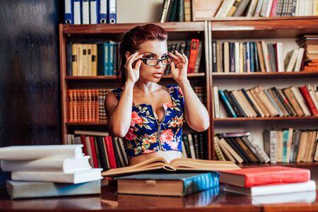a woman sits at a desk book librarian education 版權商用圖片