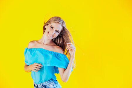 beautiful blonde girl on a yellow background in blue dress 版權商用圖片 - 134881425