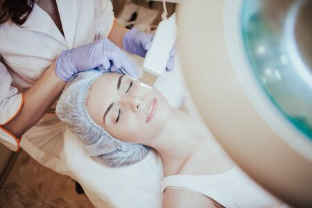 Cosmetology doctor makes the procedure a woman face cleaning