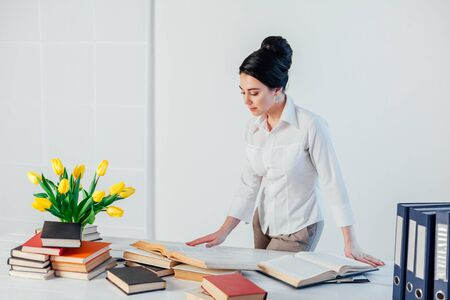 brunette woman in a business suit reads books in the Office 版權商用圖片