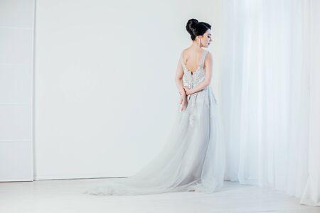 bride in wedding dress in white room