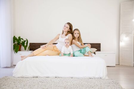 three sisters on the bed in the bedroom in the morning 版權商用圖片