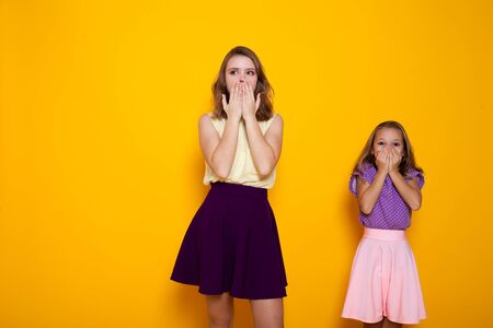 Two fashionable sisters cover their mouths with their hands