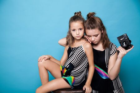 Two fashionable sisters girls with a camera on a blue background
