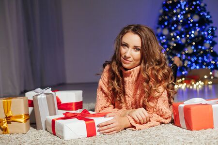 beautiful woman with gifts at the Christmas tree lights garlands new year Zdjęcie Seryjne