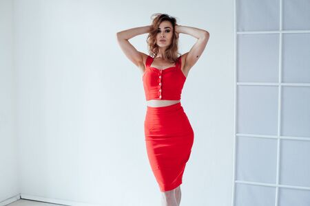Portrait of a beautiful fashionable woman in a red dress in a white room 스톡 콘텐츠