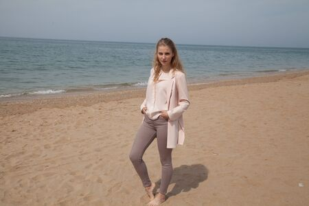 Beautiful blonde woman walks on the beach by the sea alone Imagens
