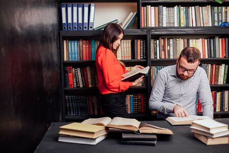 a man with a woman in the library prepared for the exam read books 1