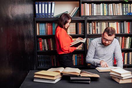 ein Mann mit einer Frau in der Bibliothek, die sich auf die Prüfung vorbereitet, las Bücher 1