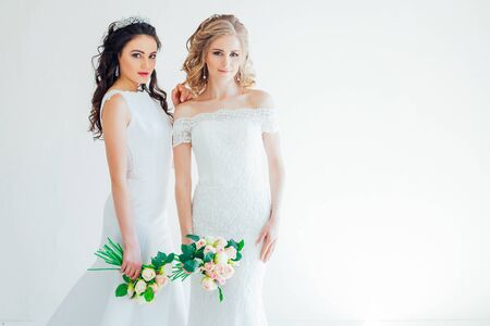 two brides in white wedding gowns flowers