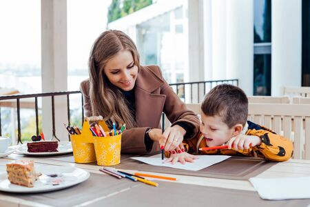 mother and son draw drawing hands colored pencils