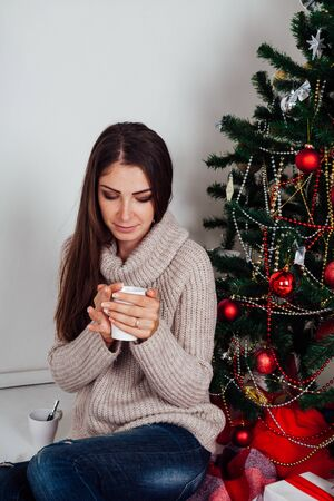 girl drinking coffee under the Christmas tree new year tea
