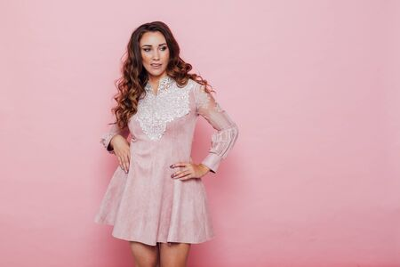 Portrait of a beautiful fashionable woman with hair curls in a pink dress