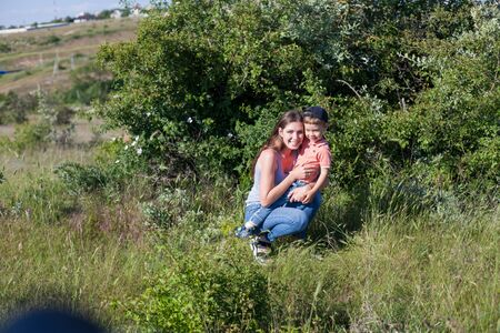 Beautiful mom with her son on a picnic rest in nature