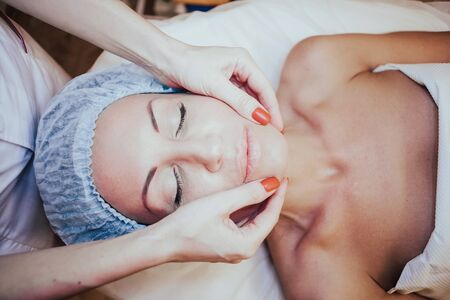 Cosmetology doctor makes woman treatments facial massage 写真素材