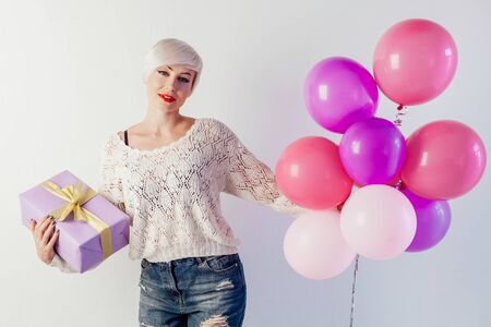 blonde girl with balloons and gift on a holiday