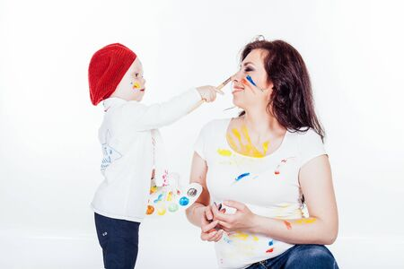 mother and little boy paints when painted Stock Photo - 137365266
