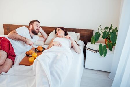 man and woman breakfast in bed morning Stockfoto