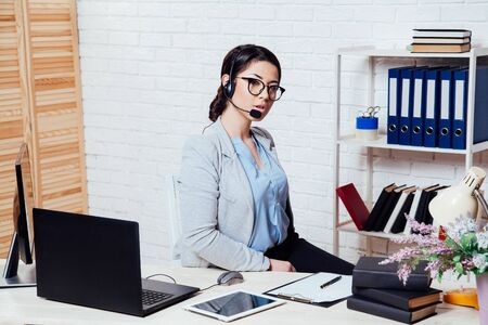 business girl Secretary sits in a white Office call center