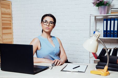 business girl sits in a white Office works at the computer