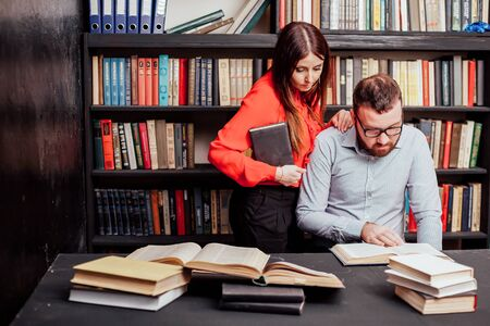a man with a woman in the library prepared for the exam read books