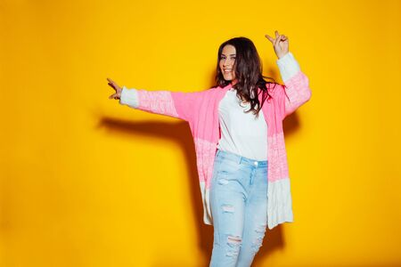 beautiful girl in colorful clothes posing on a yellow Banque d'images - 135500367