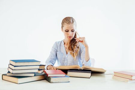 female teacher sitting at a table of many books Office Stockfoto