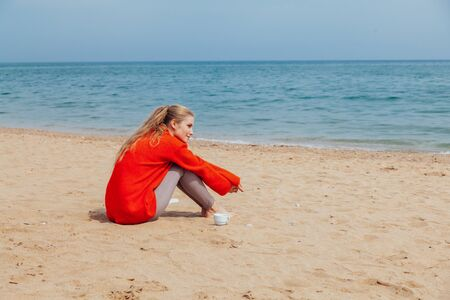 blonde sits on a sandy beach and is looking at the sea 版權商用圖片
