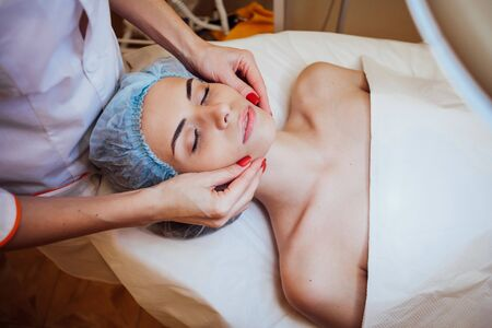 Cosmetology doctor makes woman treatments facial massage 版權商用圖片