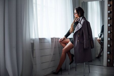 girl with gray coat sits on a Chair looking out of the window