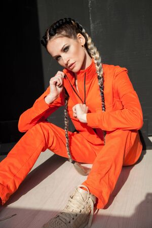 portrait of a beautiful fashionable woman with braids in orange clothes