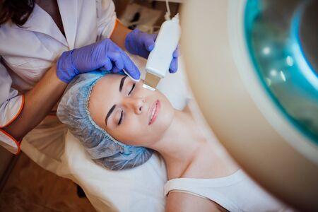 Cosmetology doctor makes woman treatments facial massage Stockfoto