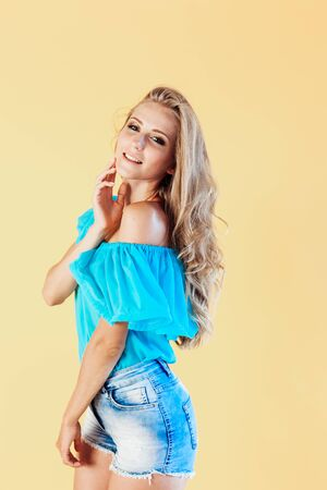 blonde girl in a blue dress, on a yellow background 版權商用圖片