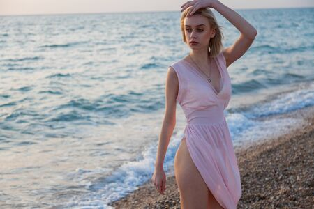 Beautiful fashionable blonde woman on the beach by the ocean