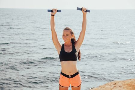 girl Sports Fitness with dumbbells on the beach Stockfoto - 135503805