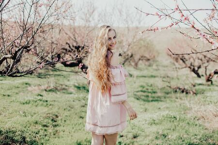 blonde in pink dress walks in the garden with flowering trees Stockfoto