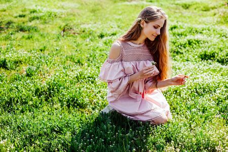 blonde girl in pink dress is collecting flowers in the garden Stockfoto