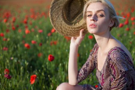 Beautiful fashionable blonde woman in a hat in a field of red flowers Banque d'images - 135503432