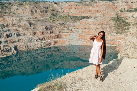 Beautiful woman with long hair in dress on cliff landscape in a journey