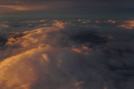 Sky with clouds at sunset from inside plane landscape