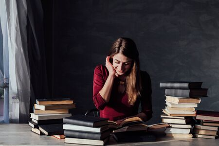 girl reading book prepares for the exam in the library