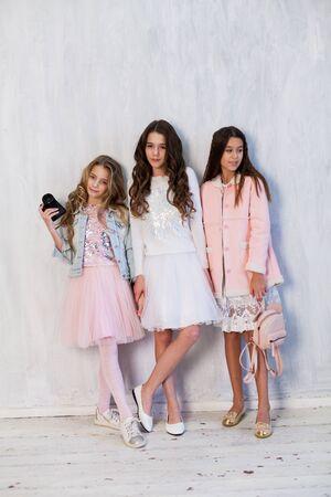 Portrait of three beautiful fashionable girlfriend girls with a photo shoot camera