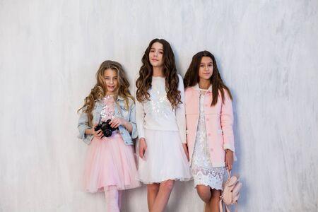 Porträt von drei schönen modischen Freundinnen mit einer Fotoshooting-Kamera