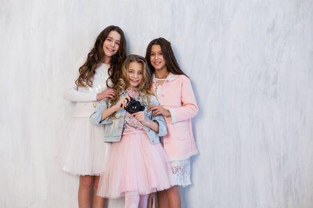 Porträt von drei schönen modischen Freundinnen mit einer Fotoshooting-Kamera Standard-Bild