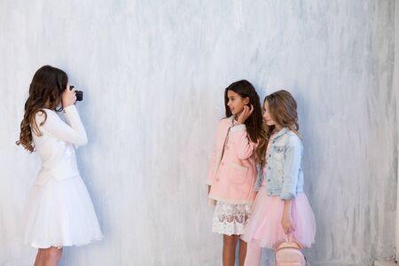 Retrato de tres hermosas chicas novias de moda con una cámara de sesión de fotos