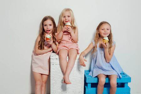 three little girls eat sweet cake with cream cupcake