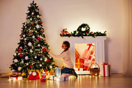 beautiful woman decorates the Christmas tree Garland lights new year holiday